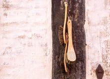 Alte Retro- Bürsten hängen dekorativ an der hölzernen Wand Stockfoto