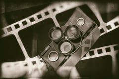 Alte Retro- Filmkamera auf Hintergrund des Perforierungsfilmes Stockfoto