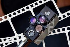 Alte Retro- Filmkamera auf Hintergrund des Perforierungsfilmes Lizenzfreie Stockbilder