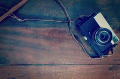 Alte Retro- Kamera auf Hintergrund des hölzernen Brettes Lizenzfreie Stockfotos