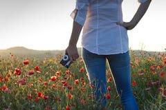 Alte Retro- Kamera in der Hand einer Frau, die auf einem blühenden Mohnblumengebiet steht Lizenzfreies Stockfoto