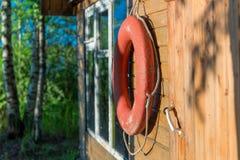 Alte Rettungsringnahaufnahme auf einer hölzernen Wand eines ländlichen Hauses Stockbild