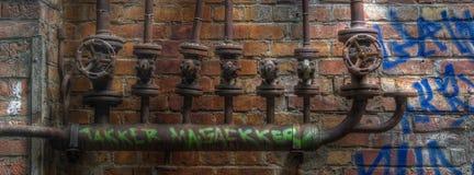 Alte Rohre mit Ventilen auf einer Wand mit Graffiti Stockbilder