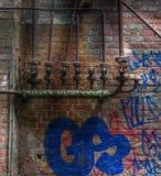 Alte Rohre mit Ventilen auf einer Wand mit Graffiti Lizenzfreies Stockbild