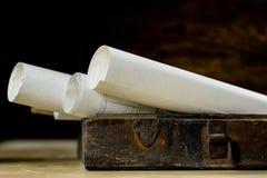 Alte Rollen und Pläne in gefalteten Papierrollen Altes Buch und Fall Dokumente auf einem alten Holztisch Lizenzfreie Stockbilder