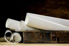 Alte Rollen und Pläne in gefalteten Papierrollen Altes Buch und Fall Dokumente auf einem alten Holztisch Stockfotos