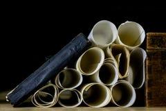 Alte Rollen und Pläne in gefalteten Papierrollen Altes Buch und Fall Dokumente auf einem alten Holztisch Stockfoto
