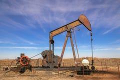 Alte rostige Ölquelle-Pumpensteckfassung, die auf dem Gebiet mit hellem blauem drastischem Himmel - Kopf von Maschinerieaussehung stockbilder