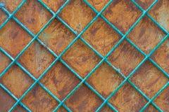 Alte rostige Eisenwand hinter einem Metall malte Gitter stockfotografie