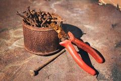 Alte rostige gebrochene Werkzeuge, Nägel und Zangen auf einem Hintergrund des Rosts Stockbild