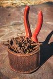 Alte rostige gebrochene Werkzeuge, Nägel und Zangen auf einem Hintergrund des Rosts Stockfoto