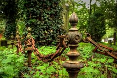 Alte rostige Geländerdocke mit Kette auf einem Friedhof Lizenzfreies Stockbild