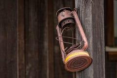 Alte, rostige Lampe, die auf Posten hängt Stockfoto