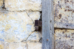 Alte rostige Schleife auf einer rostigen Eisentür geregelt in einer Steinwand Stockbild