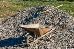 Alte rostige Schubkarre umgedreht auf einem Haufen des Bodens in einer Baustelle, Baubereich Stockfoto