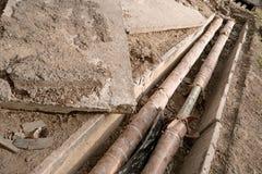 Alte rostige Wasserleitungen im konkreten Graben Untertagedienstprogramm und Zuflussrohr legen an der Baustelle reparatur Lizenzfreie Stockfotografie