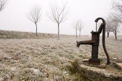 Alte rostige Wasserpumpe auf der Landschaft im Winter Lizenzfreie Stockfotos