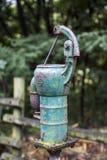 Alte rostige Wasserpumpe im Wald stockbild