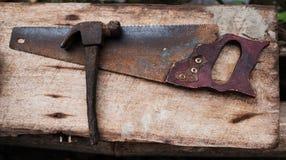 Alte rostige Werkzeuge hämmern und übergeben Säge für Arbeit Lizenzfreie Stockfotografie