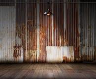 Alte rostige Zinkwand mit der Lampenbeleuchtung und -Bretterboden, ideal für Produktanzeige Stockbild