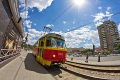 Alte rot-gelbe Tram kommt zu dem Halt von öffentlichen Transportmitteln Lizenzfreies Stockbild