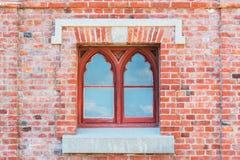 Alte rote Backsteinmauer mit Fenster Stockfotografie