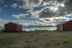 Alte rote Bootshäuser im Sommer mit schneebedecktem Berg und blauem Fjordhintergrund Lizenzfreie Stockbilder