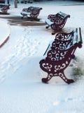 Alte rote Metallbänke im Schnee Stockbilder