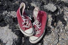 Alte rote Segeltuch-Schuhe - Asphalt Background Lizenzfreie Stockfotos