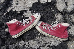 Alte rote Segeltuch-Schuhe - Asphalt Background Stockbild