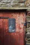 Alte rote Tür an umgeben durch Devon-Stein, Vereinigtes Königreich Stockbild