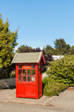 Alte rote Telefonzelle im Garten Lizenzfreie Stockfotos