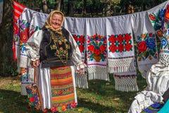 Alte rumänische Frau, die traditionelle Produkte an einer Messe verkauft Lizenzfreie Stockfotos