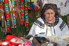 Alte rumänische Frau, die traditionelle Produkte an einer Messe verkauft Stockfoto
