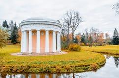 Alte runde Gebäudelaube in einem Park nahe dem Fluss im Herbst Lizenzfreies Stockfoto