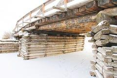 Alte rustikale Brücke über dem gefrorenen Fluss- Foto eingelassen der Winter Lizenzfreies Stockfoto