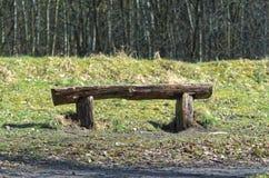 Alte rustikale Holzbank auf einem Feld mit einem Wald im Hintergrund Lizenzfreies Stockbild