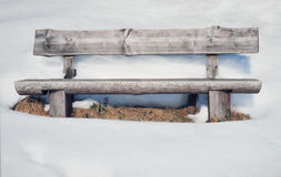 Alte rustikale Holzbank umgeben durch viele Schnee Stockbild