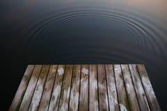 Alte rustikale Schmutzpierbrücke auf wi ein des dunklen Schwarzen des blauen Wassers See stockbilder