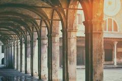 Alte Säulengangdurchgangs-Fußweise im Sonnenunterganglicht in Venedig Italien Lizenzfreies Stockfoto