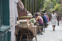 Alte Sachen für Verkauf, herausgestellt auf der Straße, auf dem Tisch ausgebreitet Vor dem hintergrund der Leute, die an den Tisc Stockbild