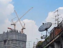 Alte Satellitendiskette gegen Bauturmstöcke Lizenzfreie Stockbilder
