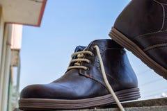 Alte scarpe marroni della caviglia per gli uomini e pronto da indossare scuri immagini stock