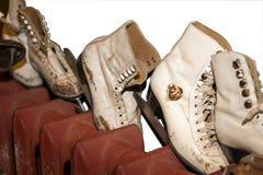 Alte schäbige Schlittschuhe, die auf dem Heizkörper lokalisiert getrocknet werden Lizenzfreie Stockbilder