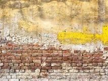 Alte schädigende Backsteinmauer mit Pflaster Lizenzfreie Stockbilder