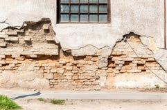 Alte schädigende Backsteinmauer mit schlechter Grundlagenbasis und abgezogenem gebrochenem Gips stürzte fast ein Stockfotografie