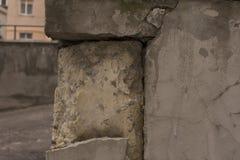 Alte schädigende Block Wand mit gebrochener weißer Gips-Schicht Stockbilder