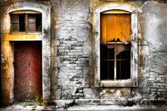 Alte schädigende Wand mit Gitterfenster und einer Tür Stockbilder