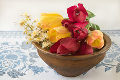Alte Schüssel mit Blumentulpen und -kastanien Stockbild