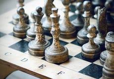 Alte Schachfiguren stehen auf dem Schachbrett lizenzfreies stockbild